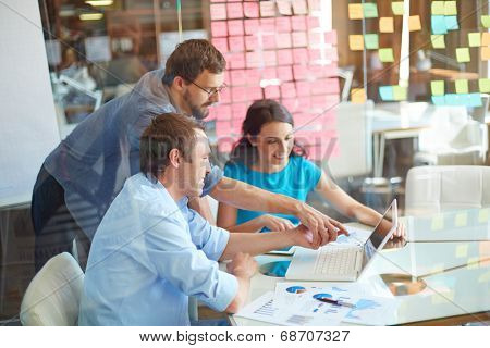 Group of three successful business partners in casual looking at laptop screen while two young men pointing at it at meeting in office