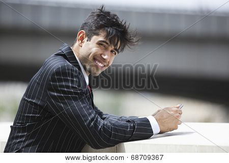 Portrait of smiling Indian businessman in pinstriped suit outdoors