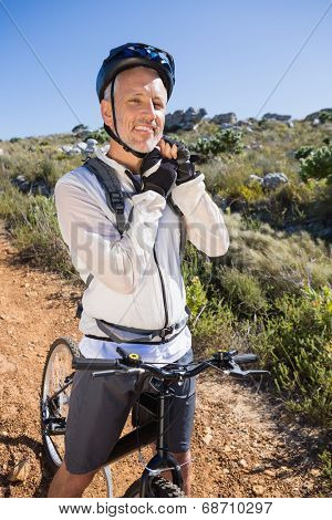 Fit cyclist adjusting helmet strap on country terrain smiling at camera on a sunny day