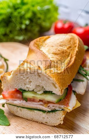 Baguette Sandwich with Lettuce,  Fresh Tomatoes, Ham, Turkey Breast and Cheese  cut in half