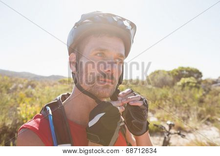 Fit cyclist adjusting helmet strap on country terrain on a sunny day