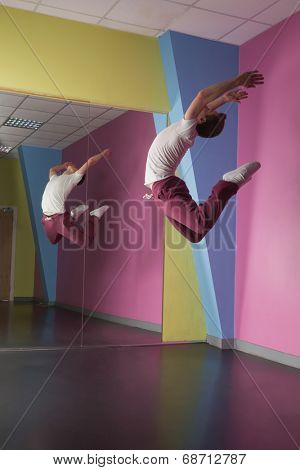 Cool break dancer mid air in front of mirror in the dance studio