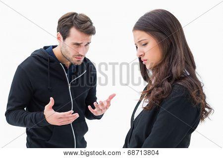 Unhappy brunette listening to boyfriend on white background