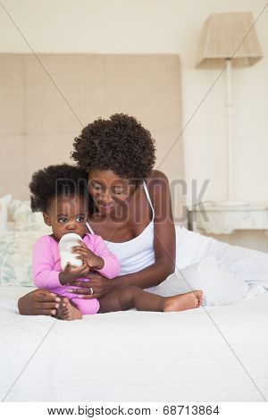 Happy mother and baby girl sitting on bed together at home in the bedroom