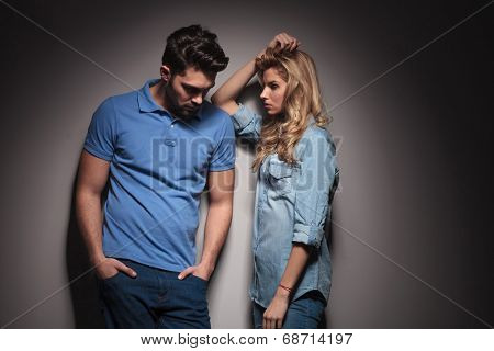sad couple standing next to each other in studio, man looking down