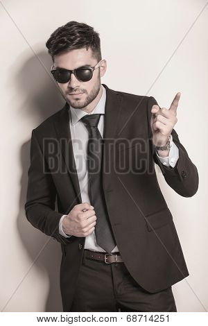 sexy young business man with sunglasses pointing his finger making the attention sign