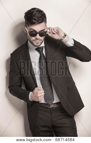 cool fashion model in suit and tie taking off his sunglasses and looking to the camera