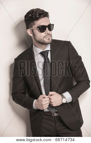 side view of a sexy business man with sunglasses holding his suit coat and looks away