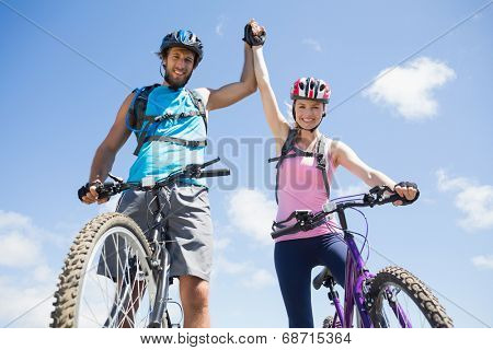Fit cyclist couple happy to have reached the summit on a sunny day