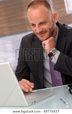 Happy businessman using laptop computer, sitting at desk.
