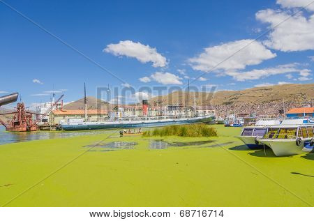 PUNO, PERU, MAY 5, 2014 - big and small boats moor in duckweed covered waters of Puno port