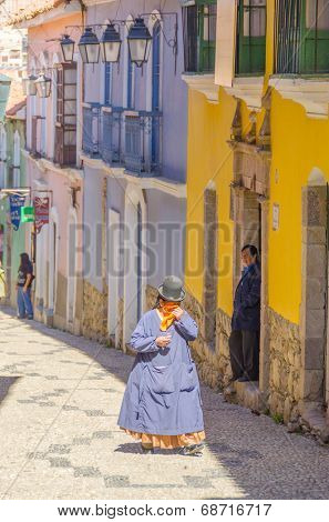 LA PAZ, BOLIVIA, MAY 8, 2014 - Local woman in traditional costume and bowler hat walks down the street Calle Jaen near museums complex