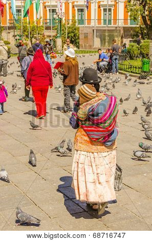 LA PAZ, BOLIVIA, MAY 8, 2014 - Local woman in traditional costume and bowler hat carries her baby in manta shawl on Plaza Murillo