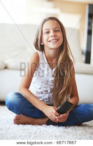 8 years old child watching tv sitting on a white carpet at home alone