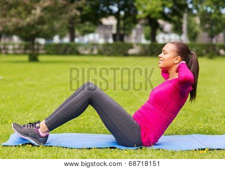 fitness, sport, training, park and lifestyle concept - smiling woman doing exercises on mat outdoors