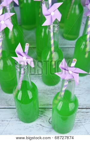 Bottles of drink with straw on wooden background