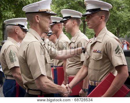 NEW YORK - MAY 23, 2014: Marine Lt. General William Faulkner shakes the hand of a U.S. Marine participating in the re-enlistment and promotion ceremony at the National September 11 Memorial site.