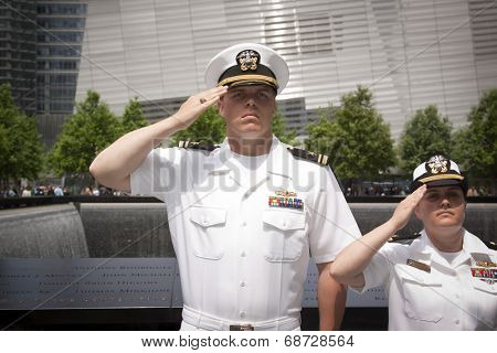 NEW YORK - MAY 23, 2014: Two US Navy sailors standing in front of the reflecting pools at the National September 11 Memorial site salute during the re-enlistment and promotion ceremony.