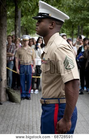 NEW YORK - MAY 23, 2014: U.S. Marine Brandon King stands at attention during the re-enlistment and promotion ceremony at the National September 11 Memorial site.