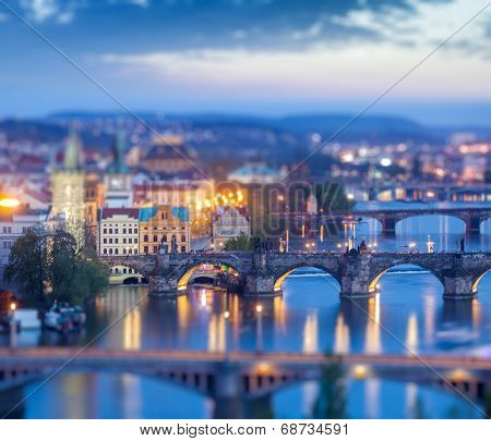Travel Prague concept background - elevated view of bridges over Vltava river from Letna Park with tilt shift toy effect shallow depth of field. Prague, Czech Republic in twilight