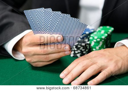 Gambler playing poker cards with chips on the table. Addiction to the gambling