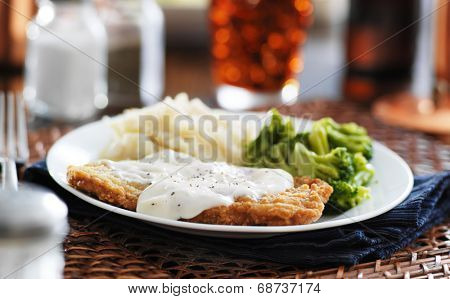 country fried steak with southern style peppered milk gravy shot in panorama style
