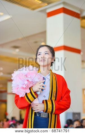 Thai college girl in academic gown is looking forward to the future in her graduation day