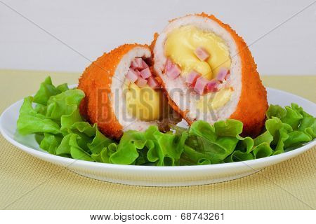 chicken cutlet with cheese, ham and salad