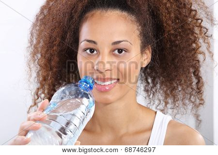 Mineral water, dark skinned girl with bottle of water