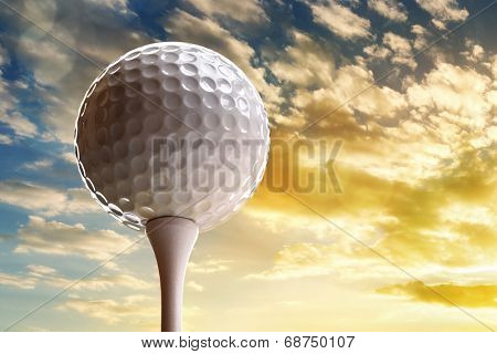 Golf ball on tee about to tee off against a sunset sky
