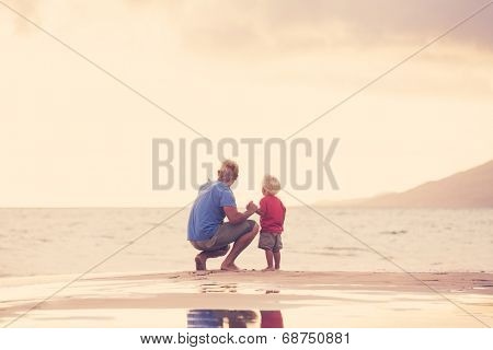 Father and son holding hands walking on the beach at sunset