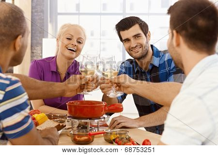 Young friends having dinner together, clinking glasses, smiling, having fun.