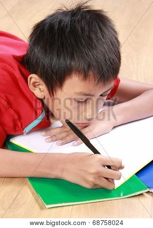 Young Boy Writing Something On The Book
