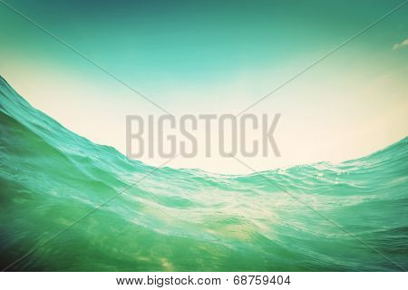 Dynamic water wave in the ocean. View from the waterline. Underwater and sunny sky. Vintage
