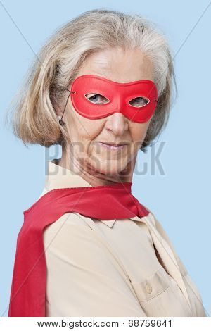 Portrait of senior woman wearing superhero costume against blue background
