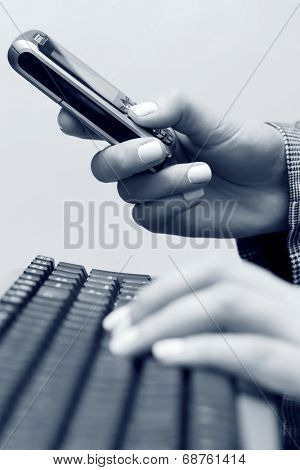 Female hands typing on computer keyboard and calling on cell phone