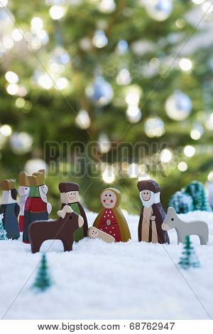 Nativity scene of Jesus birth with Christmas tree in background