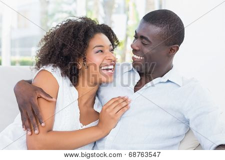 Attractive couple cuddling on the couch at home in the living room