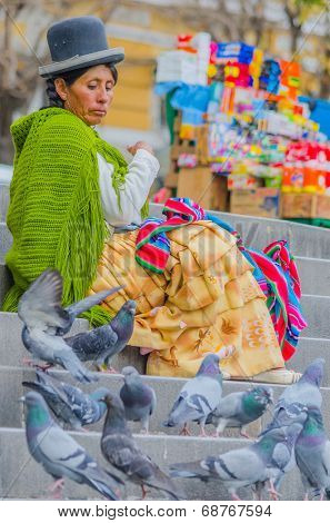 LA PAZ, BOLIVIA, MAY 9, 2014 - Local woman in traditional costume and bowler hat sits on stairs on Plaza Murillo, watching pigeons