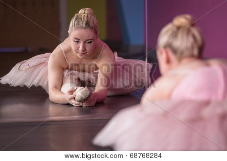 Graceful ballerina warming up in front of mirror in the ballet studio