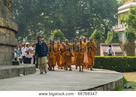 Buddhist Monks, Followed By Pilgrims, Circle The Dhamekh Stupa.