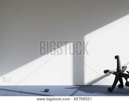 View of a broken office chair casting shadow on wall