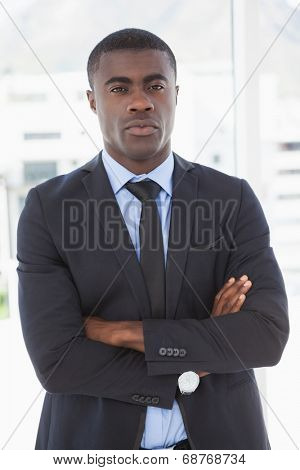 Handsome businessman frowning at camera in his office