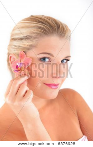 Young beautiful woman with healthy skin holding orchid flower