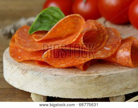 tasty spicy pepperoni sausage on a wooden board