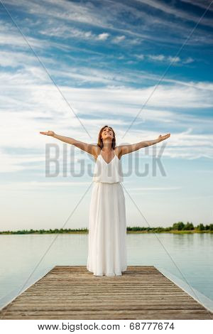 carefree female standing on stage with blue sky