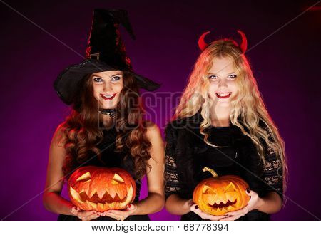 Portrait of two happy females with pumpkins looking at camera with smiles