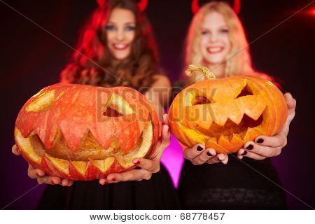 Two happy females holding carved Halloween pumpkins