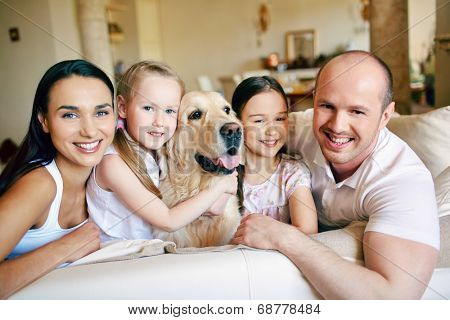 Happy family of four with dog looking at camera at home