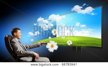 Young businessman sitting in chair behind tv with click in hand
